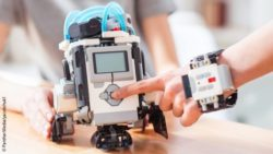 Photo: A kind of Lego robot and a child's hand that has the control for it on its wrist; Copyright: PantherMedia/yacobchuk1