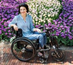 Photo: Sabine Klemens in her wheelchair in front of many flowers; Copyright: Christoph Klemens