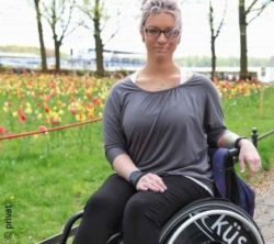 Photo: blonde woman with glasses - Janine Malik - sitting in a wheelchair in nature; Copyright: private