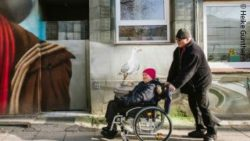 Photo: A man shoves a woman in a wheelchair; Copyright: Heike Günther