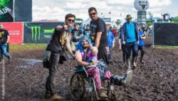 Photo: A wheelchair user and his two companions in mud in front of the festival area of the Wacken Open Airs; Copyright: Inklusion Muss Laut Sein