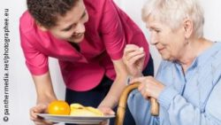 Photo: Caregiver hands over a plate with fruits to an elderly woman; Copyright: panthermedia.net/photographee.eu