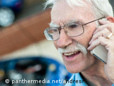 Photo: An older man talking on a mobile phone