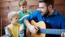 Photo: Man playing guitar, two boys are singing and clapping their hands; Copyright: panthermedia.net/pressmaster