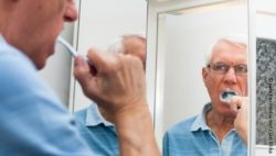 Photo: Elderly man brushing his teeth in front of a mirror; Copyright:panthermedia.net/Jan Mika