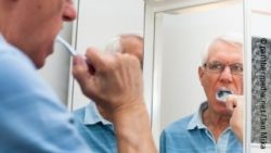 Photo: Elderly man brushing his teeth in front of a mirror; Copyright: panthermedia.net/Jan Mika