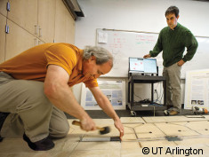 Photo: Two men test flooring with special sensors