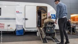 Photo: Wheelchair user enters accessible travel trailer with the help of ramps; Copyright: CamperStyle.de