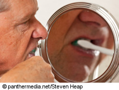 Photo: Elderly man brushing his teeth