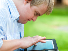 Photo: Young man with learning disabilities with a tablet