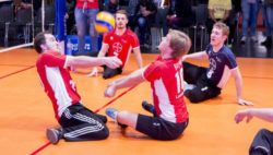 Foto: Four men playing sitting volleyball