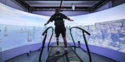 Photo: Test person with lower leg prosthesis during gait analysis on a virtual rope bridge; Copyright: TU Chemnitz/Jacob Müller