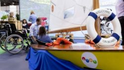 Photo: Exhibitor and visitor sitting next to an accessible small boat