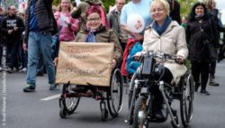 Photo: Wheelchair user at a demonstration holding a sign saying: Participation does not need skills; Copyright: Andi Weiland | Gesellschaftsbilder.de
