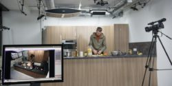 Photo: Marcus Rohrbach cuts fruits in kitchen, camera records scenes, computer screen in foreground