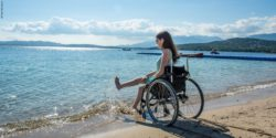 Photo: Adina Hermann at the beach in her wheelchair; Copyright: Timo Hermann