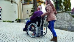 Photo: Young woman pushes elderly man in a wheelchair; Copyright: AAT
