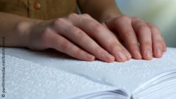 Photo: Hands on a book printed in Braille; Copyright: panthermedia.net/belchonock