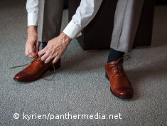 Photo: Man putting business shoes on