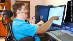 Photo: Young man in an electric wheelchair at the computer; Copyright: panthermedia.net/Bela Hoche