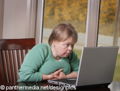 Photo: Woman with learning disability using a laptop