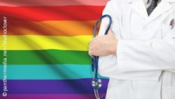 Photo: Doctor standing in front of a rainbow flag which represents the LGBT community; Copyright: panthermedia.net/Studioclover