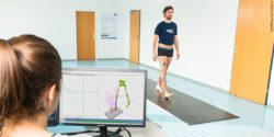 Photo: In the ReMoCap lab a woman evaluates the measured data of a man's gait analysis; Copyright: Martin Lifka Photography