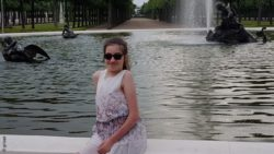 Photo: Laura Mench sits at the edge of a fountain and smiles at the camera; Copyright: private