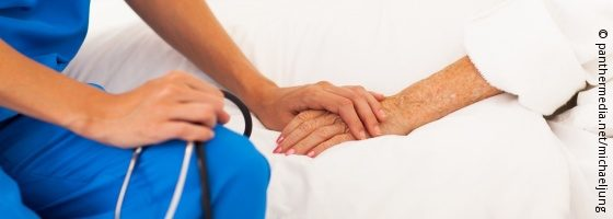 Image: Carer holds the hand of a patient; Copyright: panthermedia.net/michaeljung