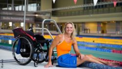 Photo: Kirsten Bruhn sitting next to wheelchair in front of a pool