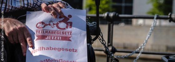 "Photo: Hands hold a paper with the words ""Teilhabegesetz jetzt!"" (Participation Law now!); Copyright: Andi Weiland 