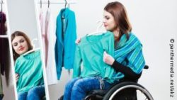 Photo: Young woman in a wheelchair trying on clothes in front of a mirror