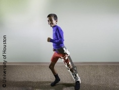 Photo: child models early-version prototype exoskeleton