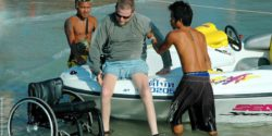 Photo: Two men help a wheelchair user to get into a boat; Copyright: panthermedia.net/Manfred Sobottka