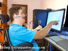 Photo: Young man in a wheelchair at a computer
