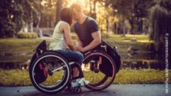Photo: Young man and young woman standing next to each other and their front heads touch, both in wheelchairs; Copyright: panthermedia.net/Vladimirs Poplavskis