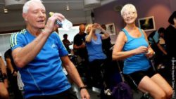 Photo: Elderly man and woman in the break of a spinning class. He is drinking water, she is smiling at him; Copyright: Andrea Hegdahl Tiltnes, NTNU