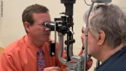 Photo: Carl W. Baker, M.D., during a vision control with a study participant; Copyright: Brooksie Beard
