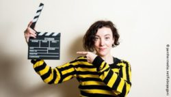 Photo: Young woman pointing on a clapperboard in her hand; Copyright: panthermedia.net/Fabiopagani