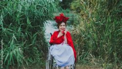 Photo: Young wheelchair user in a green setting with a somewhat more extravagant outfit; Copyright: PantherMedia/spongePo
