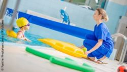 Photo: Young girl during rehabilitation in a swimming pool. The physiotherapist is sitting at the edge of the pool; Copyright: PantherMedia/welcomia (YAYMicro)