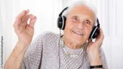 Photo: Elderly woman enjoying music she listens to via headphones; Copyright: PantherMedia/AndreyPopov