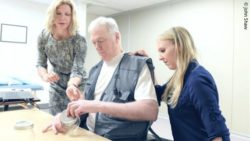 Photo: a male stroke patient is sitting at a table, doing some finger exercises, two women standing beside him; Copyright: John Shaw