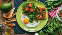 Image: A fried egg with tomato salad on a plate; Copyright: PantherMedia/VadimVasenin