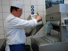 Photo: Man prepares the dishwashing conveyor