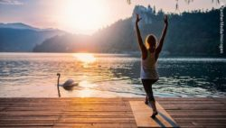 Photo: A woman at a lake doing yoga; Copyright: PantherMedia/microgen
