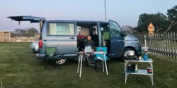 Photo: Michel Arriens sitting in front of his converted VW Bulli bus on a camping site; Copyright: privat