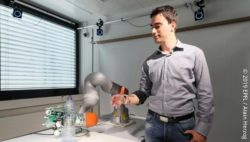 Photo: A man tries out shared control with the robotic arm.; Copyright: 2019 EPFL / Alain Herzog