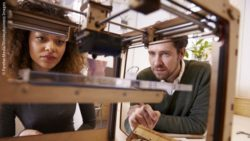 Photo: A woman and a man are watching the 3D printing process; Copyright: PantherMedia/Monkeybusiness Images