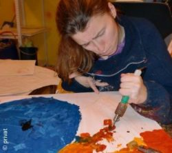 Photo: Woman - Annette Jablonski - concentrated while painting with a kind of thick brush; Copyright: privat